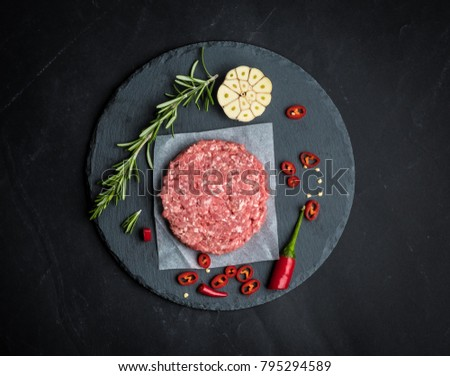 Raw burger beef patty with rosemary and garlic on dark cooking background