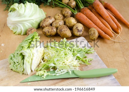 Raw carrot, new potatoes and cut cabbage  vegetable on a table ready for soup.  - stock photo