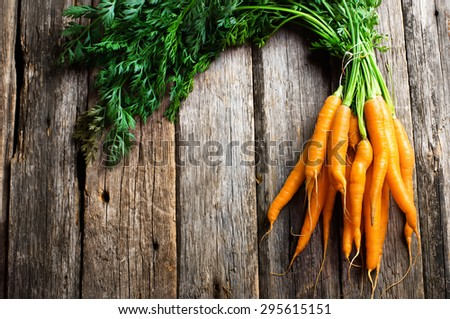 Raw carrot with green leaves on wooden background - stock photo