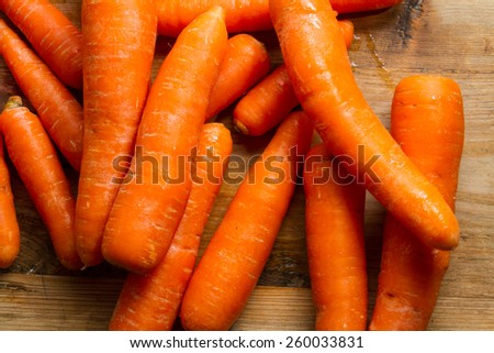 Raw carrots against a rustic wooden background. - stock photo