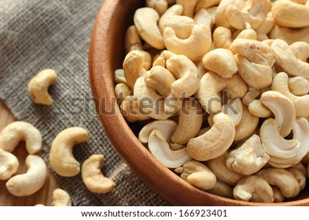 Raw cashews close-up in wooden bowl on sackcloth - stock photo