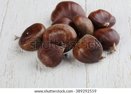Raw Chestnuts heap on the wood  background