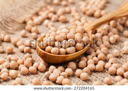 Raw chick peas organic vegetarian nutrition super food in wooden spoon on textile background - stock photo