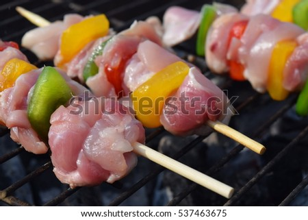 Raw chicken and vegetable skewers on the outdoor barbecue