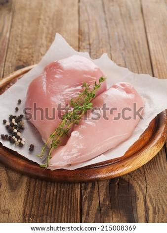 Raw chicken breast with thyme and peppercorns, selective focus. Culinary cooking ingredients.  - stock photo