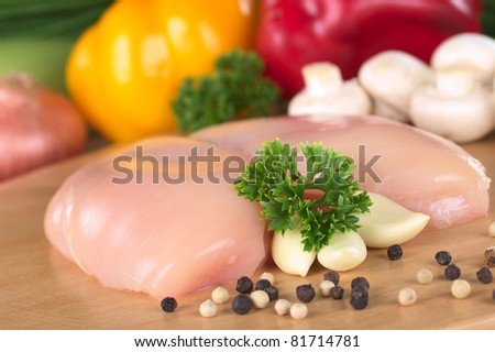 Raw chicken breast with white and black pepper corns, parsley leaf and garlic and with some fresh vegetable in the back (Selective Focus, Focus on the front of the meat and the parsley) - stock photo