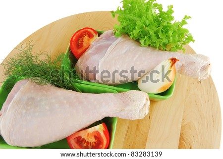 raw chicken drumstick on wooden plate on white - stock photo