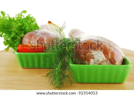 raw chicken drumstick on wooden plate on white