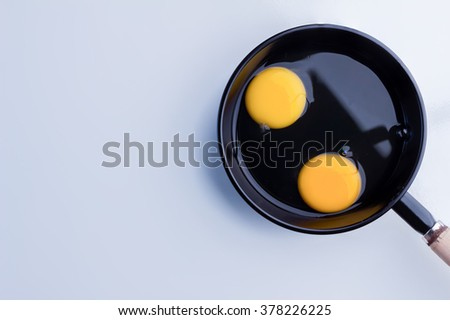 Raw chicken egg in a frying pan with copy space - stock photo