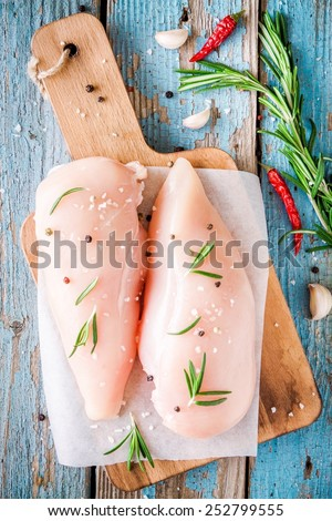 raw chicken fillet with garlic, pepper and rosemary on a blue wooden background - stock photo