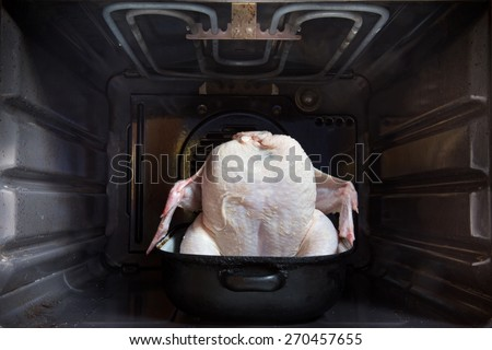 raw chicken in a roasting pan in oven - stock photo