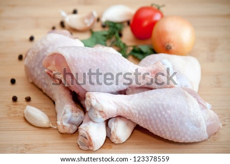Raw chicken legs with vegetables and spices on the chopping board - stock photo