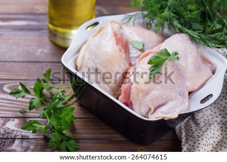 Raw chicken meat in bowl  on dark table. Selective focus. Rustic style.  - stock photo