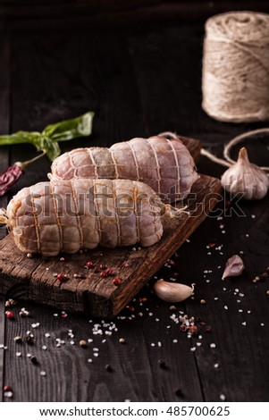 Raw Chicken roll with salt,basil and garlic on a wooden background