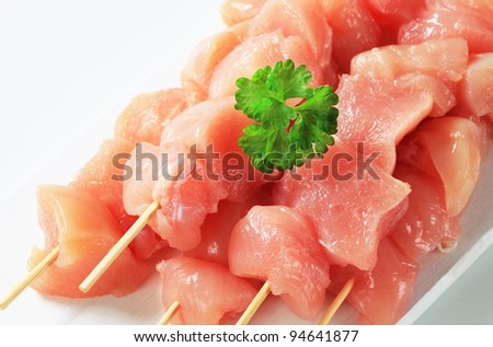 Raw chicken skewers on cutting board  - stock photo