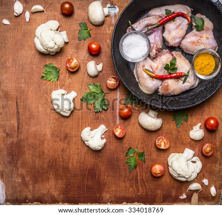 Raw chicken wings with salt and pepper tomorrow spices on an old cast-iron skillet mushrooms Cauliflower Cherry tomatoes and parsley on wooden rustic background top view - stock photo