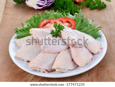 Raw chicken wings with vegetables on wooden board - stock photo