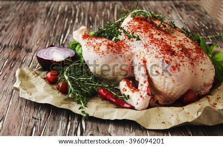 raw chicken with herbs spices ingredients, ready for cooking, on a wooden table, selective focus - stock photo