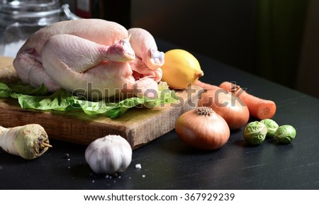 Raw chicken with vegetables on black background - stock photo