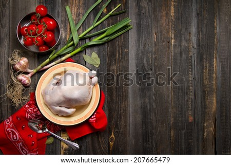 Raw chicken, young garlic, tomatoes and spices in a rustic style - stock photo
