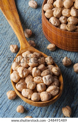 Raw chickpeas in a wooden spoon close-up on an old table - stock photo