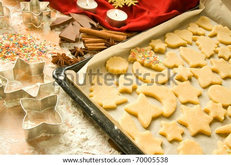 Raw Christmas cookies on a baking sheet being decorated - stock photo