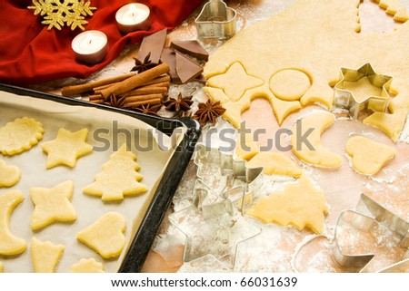 Raw Christmas cookies on a baking sheet with dough being cut out with Christmas related shapes - stock photo