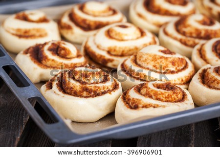 Raw cinnamon rolls. Preparation process - unbaked dough, waiting befor baking  - stock photo