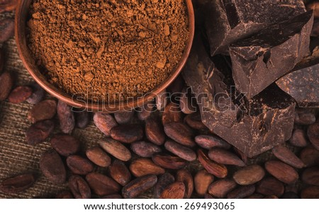 Raw cocoa beans, clay bowl with cocoa powder, black chocolate on brown sacking, top view - stock photo