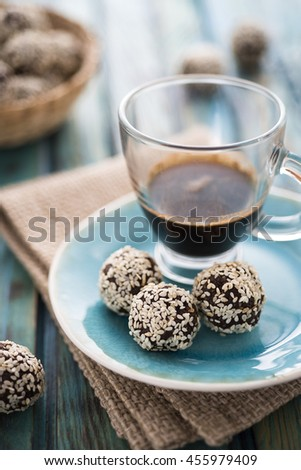 Raw cocoa candies with sesame seeds and a cup of coffee - stock photo