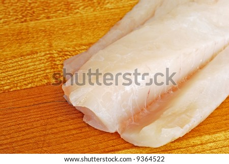 Raw Cod on a wooden butcher block - stock photo