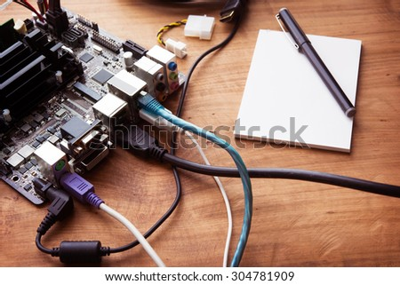 Raw computer board connected with various cables and connectors. Electronic project or prototype making. Bare computer circuit board hooked up on a work table. - stock photo