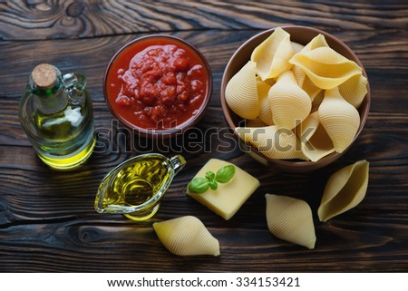 Raw conchiglioni with tomato sauce, olive oil and parmesan, high angle view - stock photo