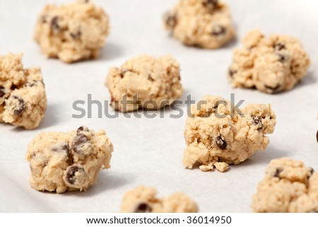 Raw cookie dough on a baking sheet with parchment - stock photo