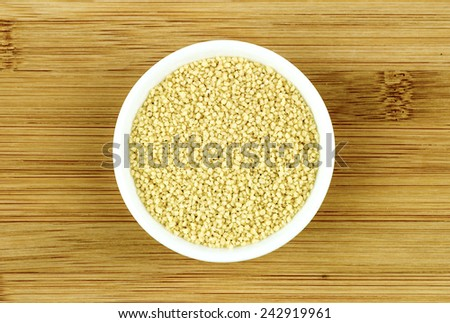 Raw couscous in bowl on wooden background - stock photo