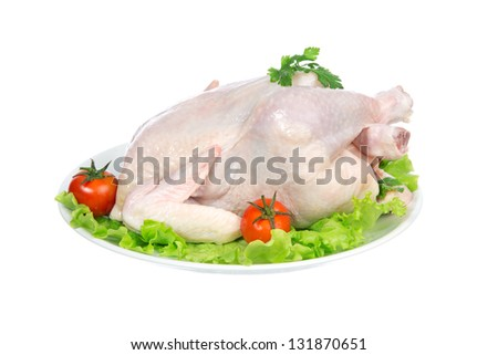 Raw crude chicken on a plate garnished with vegetables salad, tomatoes and greens isolated on a white background - stock photo
