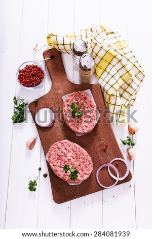 Raw cutlets of minced meat on a wooden cutting board, top view. - stock photo