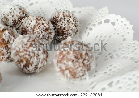 Raw dates and coconut candy on paper lace