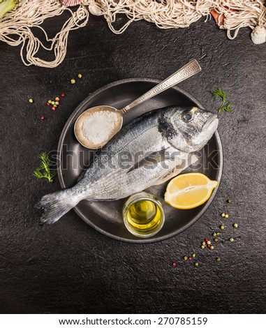 Raw dorado fish in gray rustic plate with lemon,oil and spoon of salt on dark stone background, top view - stock photo