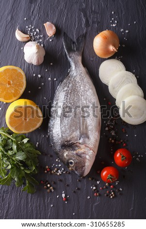 Raw dorado fish with ingredients on a table. vertical top view - stock photo