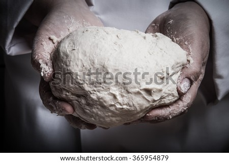 Raw dough in a chef hands. Toned. - stock photo
