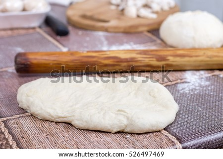 Raw dough on the table with rolling pin