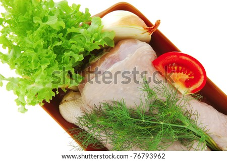 raw drumstick with lettuce and tomatoes over white - stock photo