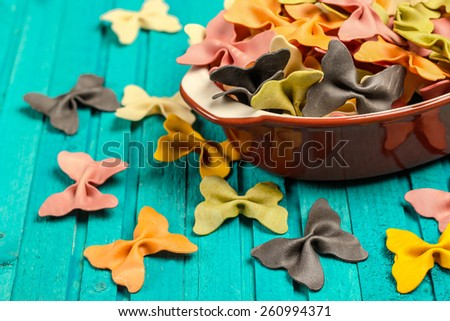 Raw, dry italian pasta in a ceramic bowl on a wooden background. Selective focus - stock photo