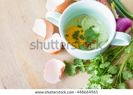Raw egg in a green bowl and garnish - stock photo