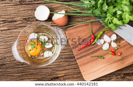 raw egg in bowl and vegetable on wood background, prepared food for breakfast. - stock photo