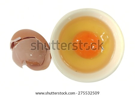 Raw egg in cup and broken egg shell on white background