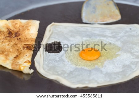 Raw egg on roti or chapati on the hot flying pan, street food in Thailand.