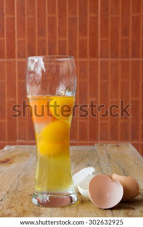 Raw Egg with Yellow Yolk in a glass and Broken Shell Halves  - stock photo