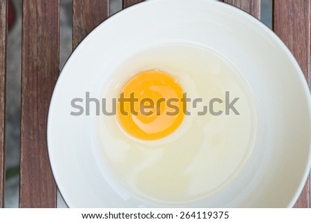 raw egg yolk on the dish on table - stock photo